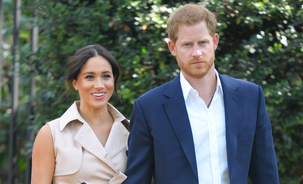 Prince Harry in a blue suit outdoors with Meghan Markle in a tan outfit