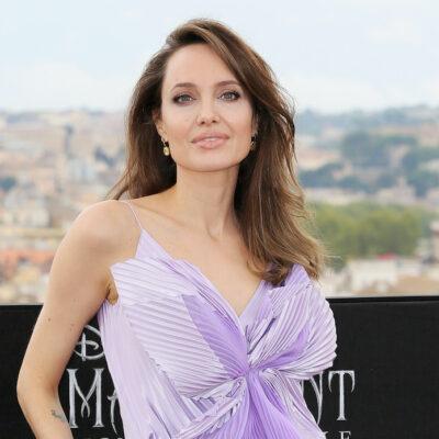 Angelina Jolie smiling in a purple dress