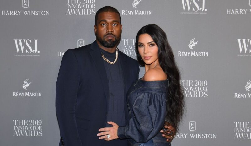 Kanye West in a navy suit with Kim Kardashian in a navy outfit