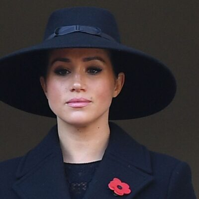 Meghan Markle in a black dress and black hat