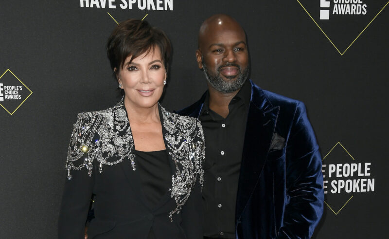 Kris Jenner in a black and silver outfit with Corey Gamble in a blue suit