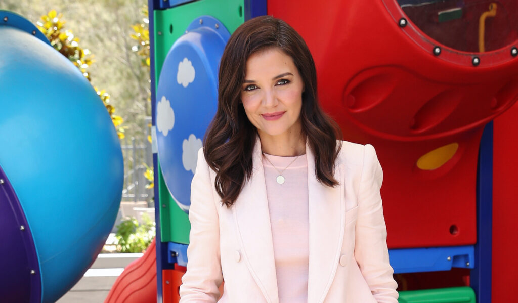Katie Holmes smiling in a pink blazer and shirt outdoors