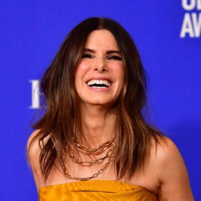 Sandra Bullock laughing in a yellow dress