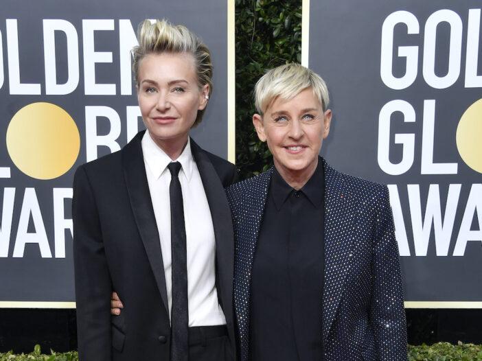 Portia de Rossi in a black suit with Ellen Degeneres in a blue suit