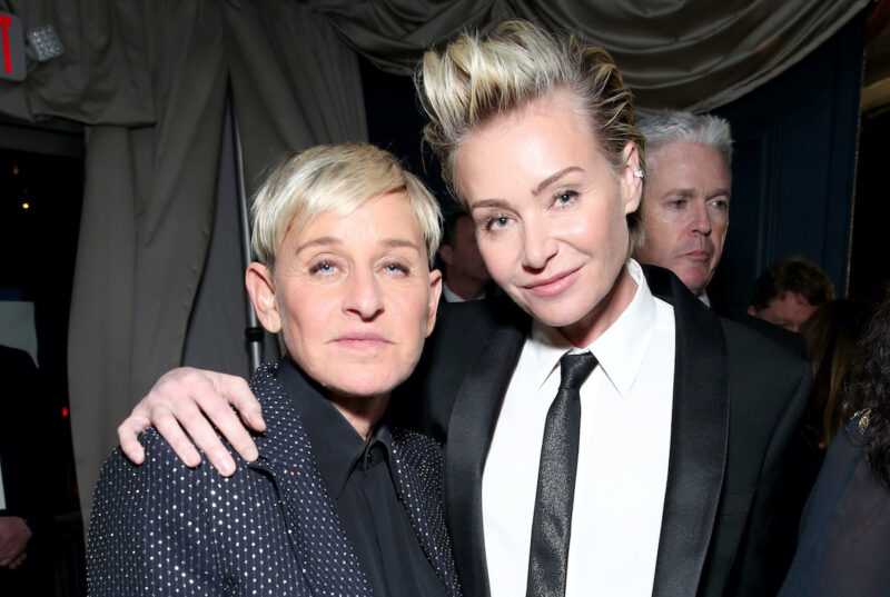 Ellen DeGeneres in a blue suit with Portia de Rossi in a black suit