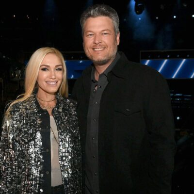 Blake Shelton in a black jacket with Gwen Stefani in a shiny silver jacket