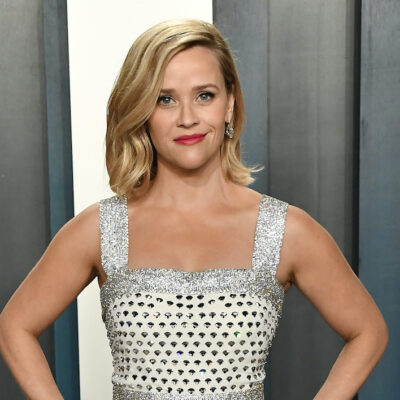 Reese Witherspoon in a white and silver dress with hands on hips