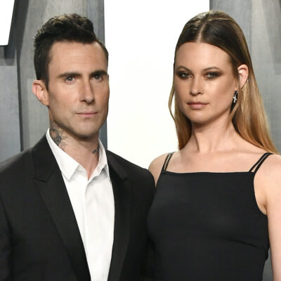 Adam Levine in a black suit with Behati Prinsloo in a black top