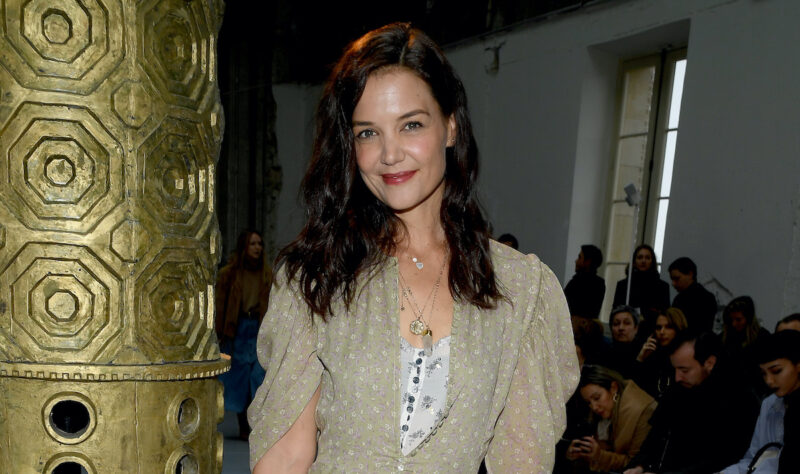 Katie Holmes smiling in a gold and white outfit