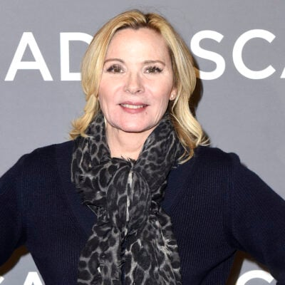 Kim Cattrall smiling in a blue top with scarf