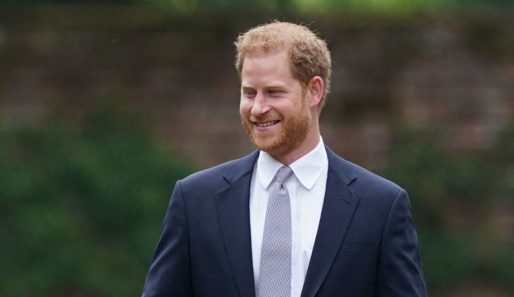 Prince Harry smiling outside in a blue suit