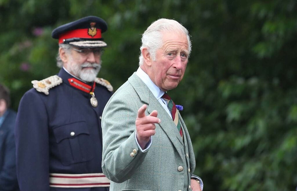 Prince Charles points in a grey-green suit