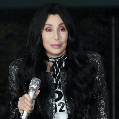 Cher holding a microphone in a black jacket