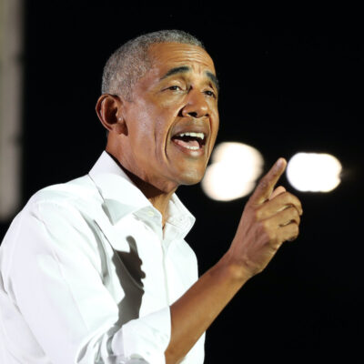 Barack Obama in a white shirt speaking at a podium
