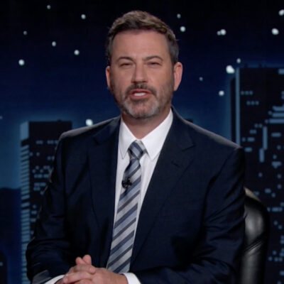 Jimmy Kimmel in a suit sitting at a desk
