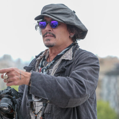 Johnny Depp in a grey coat and hat outdoors