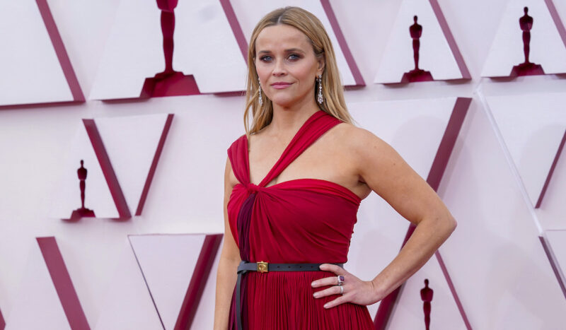 Reese Witherspoon with hand on hip in a red dress