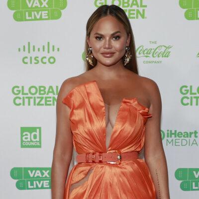 Chrissy Teigen smiling in an orange dress
