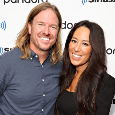 Chip Gaines on the left with long hair, standing with Joanna Gaines.