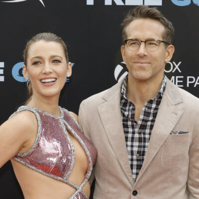 Blake Lively in a pink dress with Ryan Reynolds in a tan coat