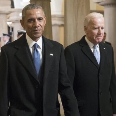 Barack Obama and Joe Biden walking together in black suits