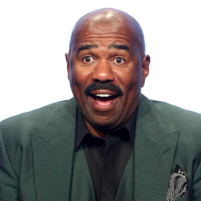 Steve Harvey smiling in a green suit