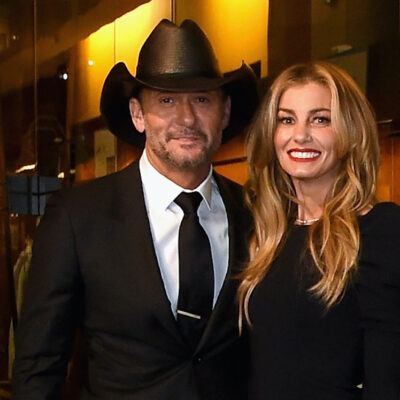 Tim McGraw smiling in a suit and cowboy hat with Faith Hill in a black dress