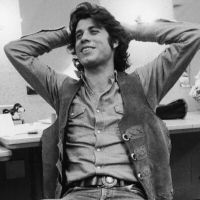 Black and White photo of John Travolta in the late 1970s with his hands behind his head.