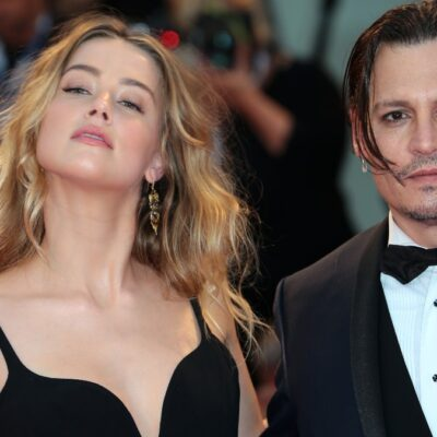Amber Heard wears a black dress and tosses her hair as she stands next to Johnny Depp, in a black tux, on the red carpet