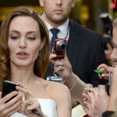 Angelina Jolie holding a phone in a scrum of reporters. She set the record for Instagram followers.