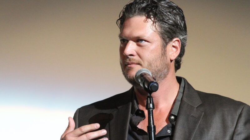 Blake Shelton wears a dark colored suit as he gives remarks onstage