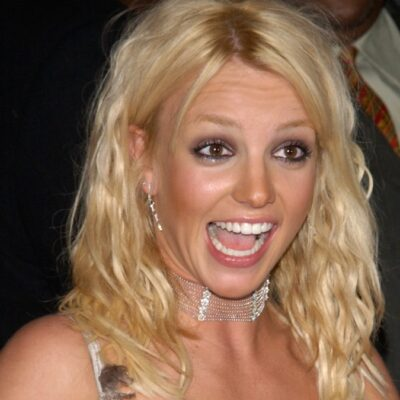 Britney Spears smiles at someone off camera while walking the red carpet