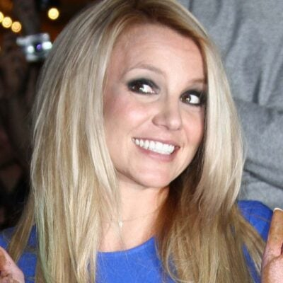 Britney Spears wears a blue dress and holds up her hands