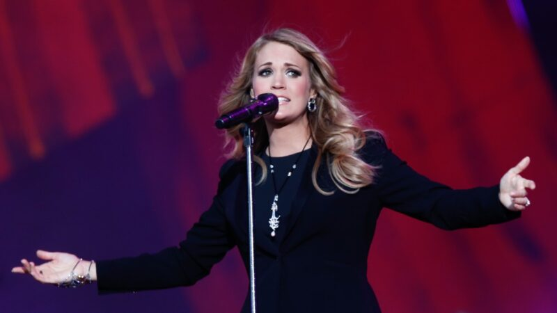 Carrie Underwood wears a black dress as she performs onstage