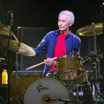 Charlie Watts in a pink tee shirt and blue button down, playing drums on stage.