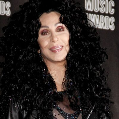 Cher wears a large black wig, leather jacket, and sparkly one-suit on the red carpet