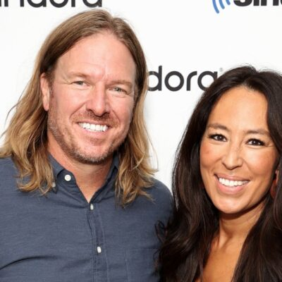 Chip, in a gray shirt, and Joanna Gaines, in a black blazer, pose on the red carpet