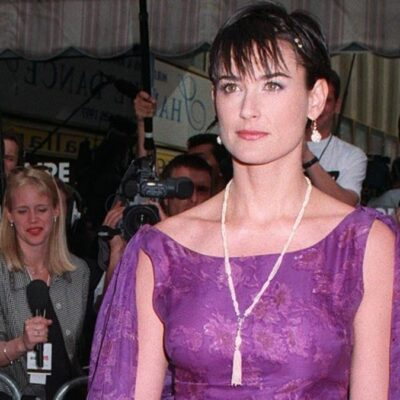 Demi Moore wears a purple gown while attending the Cannes Film Festival in 1997