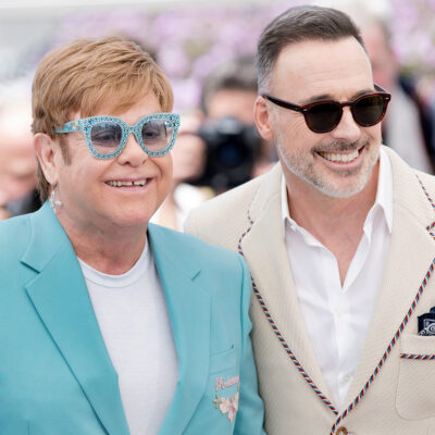 Elton John on the left in a turquoise suit and glasses, David Furnish on the right.