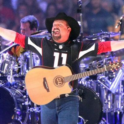Garth Brooks performing on stage at a stadium concert.