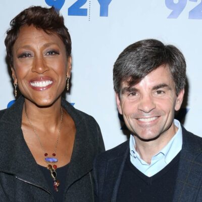 Robin Roberts, in all black, stands with George Stephanopoulos, in a dark blazer, pose together against a white background