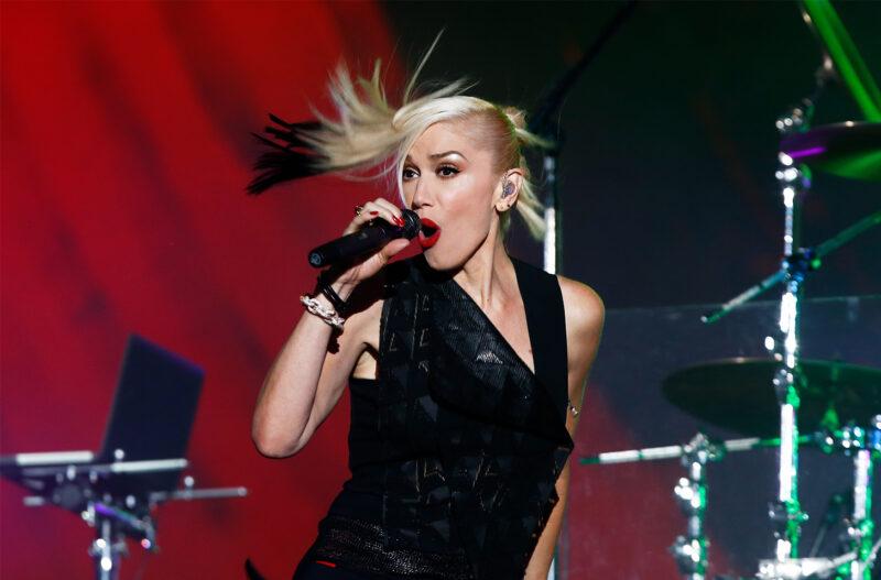 Gwen Stefani in all black, performing on stage.