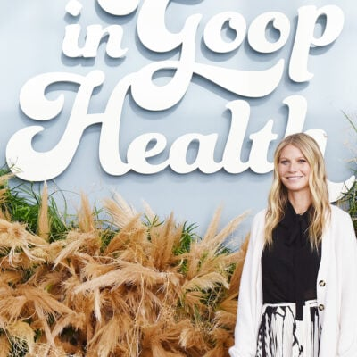 Gwyneth Paltrow standing in front of a Goop sign