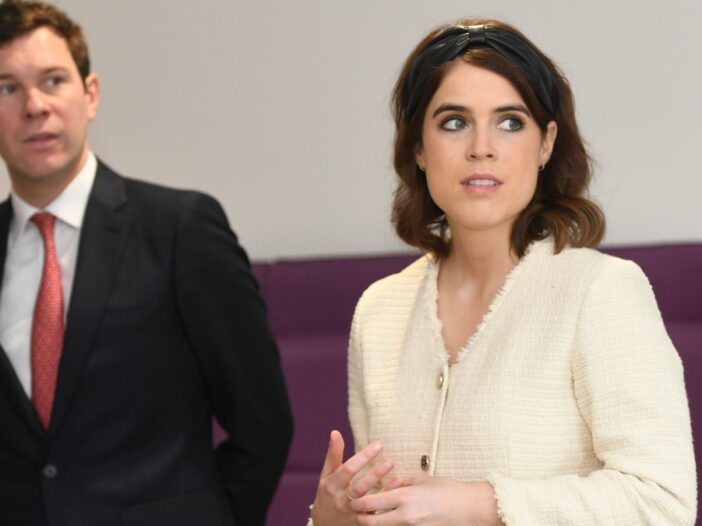 Jack Brooksbank wears a black suit and stands slightly behind his wife, Princess Eugenie, in a cream blouse