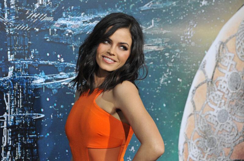 Jenna Dewan looking over her shoulder, wearing an orange dress