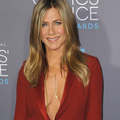 Jennifer Aniston smiling in a low cut red top