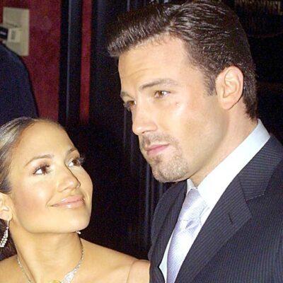 Jennifer Lopez gazes up at Ben Affleck, in a dark suit, on the red carpet