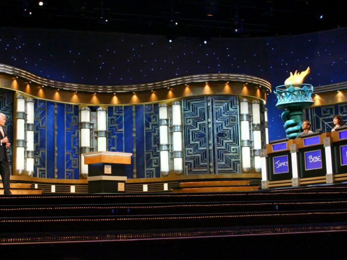 Host Alex Trebek faces three contestants on the stage of Jeopardy!