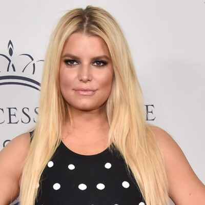 Jessica Simpson wears a black dress with white spots in front of a white background