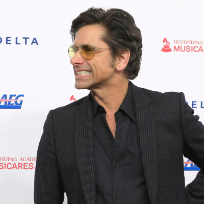 Jphn Stamos in sunglasses, looking to the right and grimacing.
